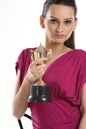 Beautiful teenage girl with gold trophy photo