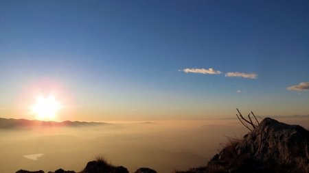 Sunset on the top of the mountain with layer of clouds and bright blue colored sky in the background
