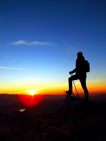 On the top with backpack and poles