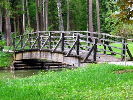 wooden bridge: Wooden bridge over pond with green grass Stock Photo