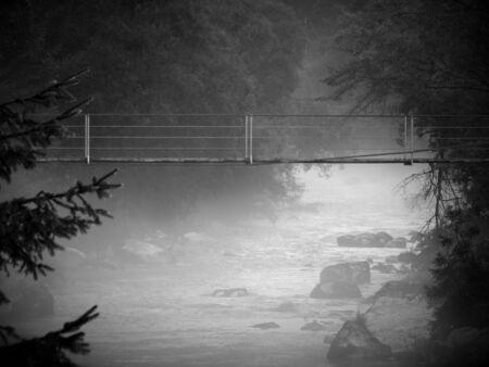 hazy: Wooden suspension bridge over hazy river