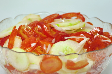 Salad with red tomato and gherkins in a bowl Stock Photo