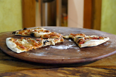 Pizza slices on wooden plate