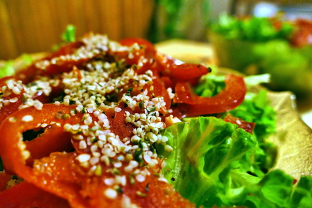 Salad with red paprika and green lettuce on table - closeup