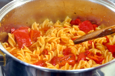 Pasta with red paprika in bowl - side view