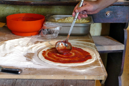 Cook putting tomato sauce on pizza dough