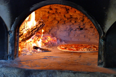 Pizza in wood fired oven - traditional, rustic way of making pizza