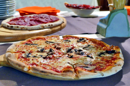 Pizza with mushrooms and olives on table