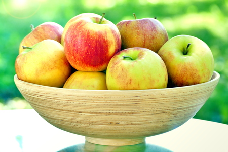 Organic apples in basket on table. Fresh apples in nature. Stock Photo