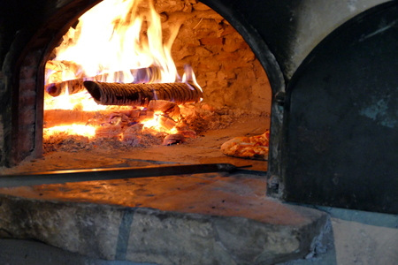 Cook putting pizza in wood fired oven Stock Photo
