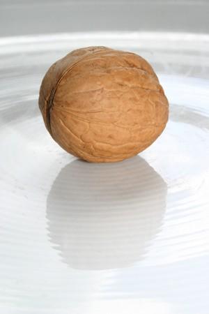 nutshell: Walnut with nutshell on a white dish