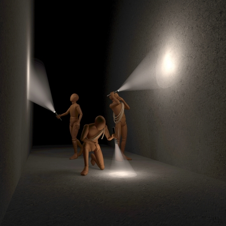 Three figures, men investigating room, cave, tunnel in the dark with flashlights Stock Photo