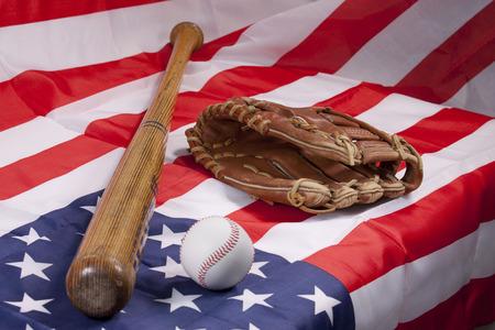 sporting equipment: Baseball bat and glove on American flag Stock Photo