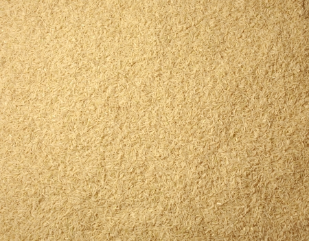Brown long rice background, uncooked raw cereals, macro closeup