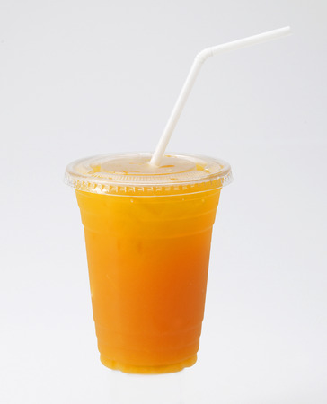 Orange Juice in cup with straw on white background