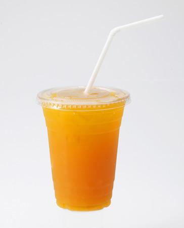 jugos: Zumo de naranja en taza con paja en el fondo blanco