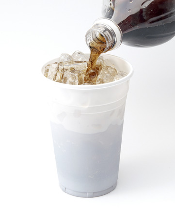 Filling Plastic Cup with cola from a bottle on white background Stock Photo