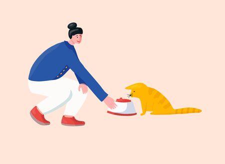 Girl volunteer feeding lost cat in animal shelter.