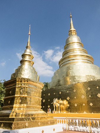 two big beautiful Gold pagondas in Prasing temple thai people called wat-Pra-Sing landmark of Chiangmai ,Thailand with clear blue sky
