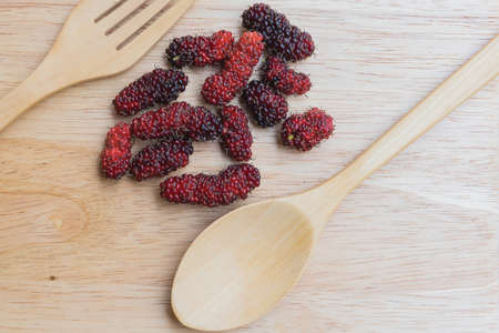 Mulberry spoon and fork on a wood plant, mulberry have Red and black color and  berry fruit good health Stock Photo