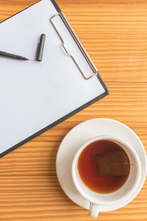 A cup of tea or coffee and a pen and notebook on wooden desks in office Banco de Imagens