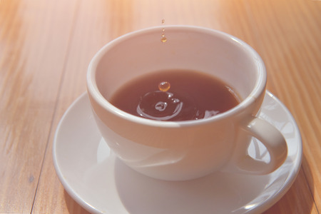 good time or morning Tea drop in a cup on the wooden table. soft focus