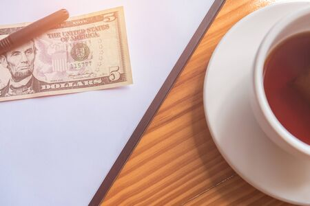 a pen and dollar bank placed on paper note and tea or coffee cup on the side on the wooden table background.