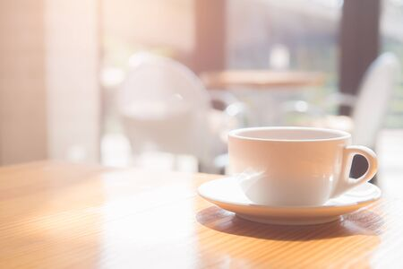 good morning a tea or coffee cup on wooden table in coffee shop. soft focus Stock Photo