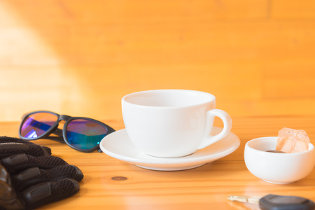 driving glove and glasses place near tea cup on the wooden table