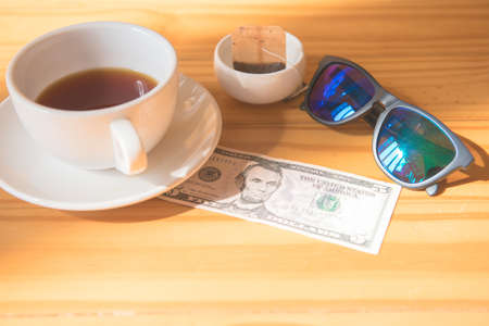 make money tip dollar or euro for travel and tea cup near on the wooden table Stock Photo