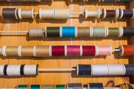 Colorful thread spools show on wooden table close up. Sewing string, handicraft concept