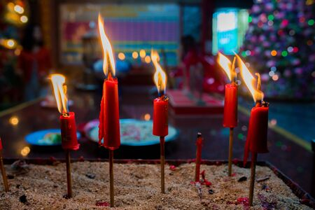 Burning candle in Chinese temple on bright or darkness background