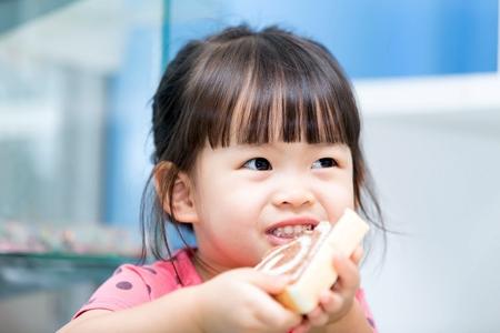 Asian cute girl eating bread Фото со стока