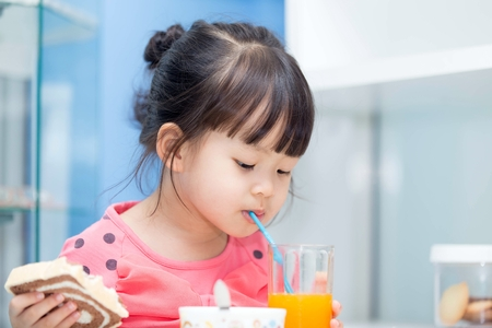 Asian girl sucking juice from a glass in one hand and bread. Фото со стока