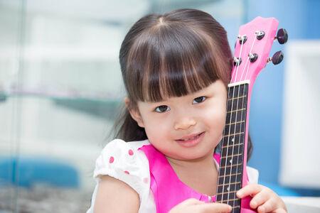 Asian girl sitting happily hugging pink ukulele Фото со стока