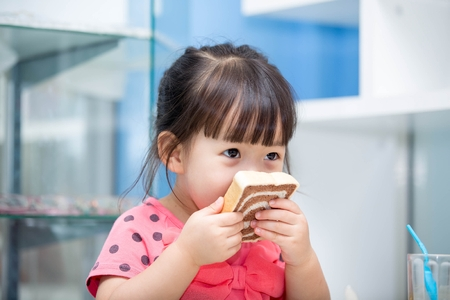 eating pastry: Asian cute girl eating bread Stock Photo