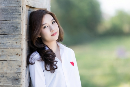 Asian woman smiling happy on sunny summer or spring day outside in park Фото со стока