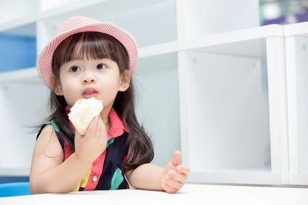 Asian cute girl eating bread. Фото со стока