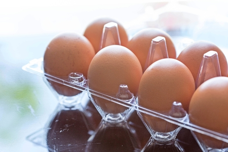 chicken eggs in plastic package on the table backdrop of natural light in the morning. Фото со стока
