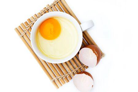Top view egg yolk in white bowl and broken egg shells on white background