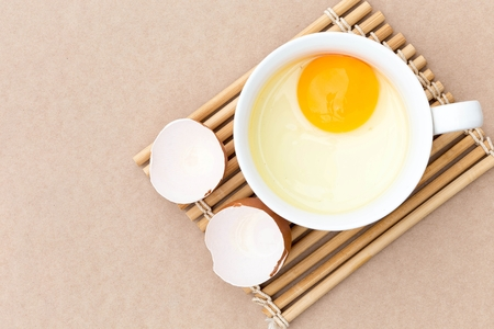 Top view egg yolk in white bowl and broken egg shells