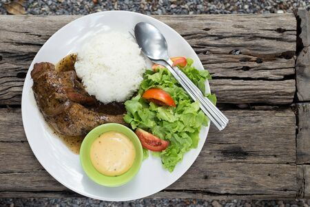 Black pepper chicken served with rice and salad.