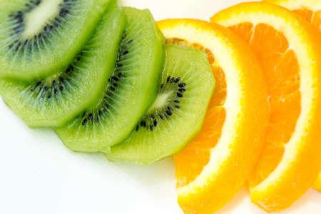 sliced fruit: sliced Kiwi fruit and citrus Orange placed in a white dish. Stock Photo