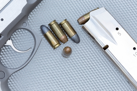 calibre: Close up of 9 mm. bullets with 9 mm. handgun in background
