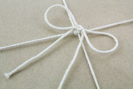 pack string: Tied in a bow on a brown recycled paper package Stock Photo