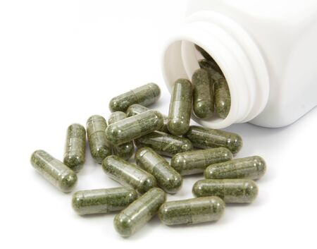 eastern medicine treatment: herb capsules spilling out of a bottle  isolated on white