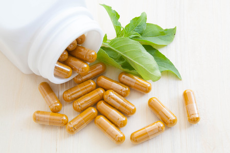 eastern medicine treatment: herb capsules spilling out of a bottle