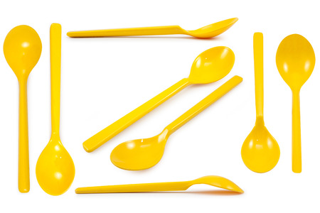 Collection yellow plastic spoons isolated on white background