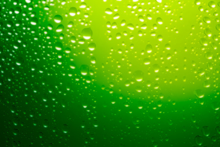refreshed: green water drops on glass background