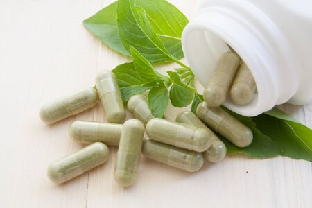 herb capsules spilling out of a bottle